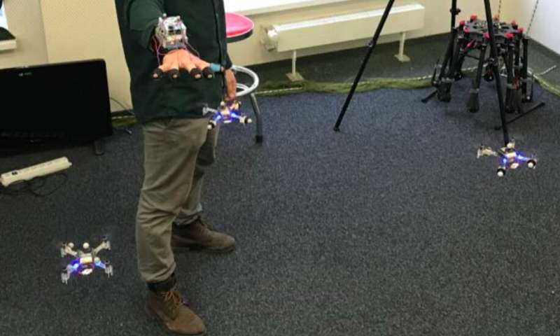 SwarmTouch: a tactile interaction strategy for human-swarm communication