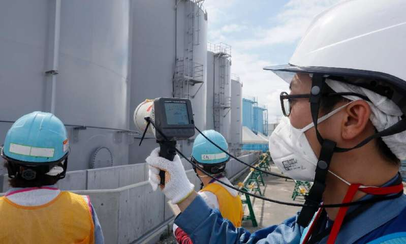 Staff measure radiation levels around the storage tanks of radiation-contaminated water at the tsunami-crippled Tokyo Electric P